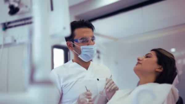 En kvinne som får undersøkt tennene hos tannlegen etter at hun har fått ødelagte tenner som følge av en yrkesskade