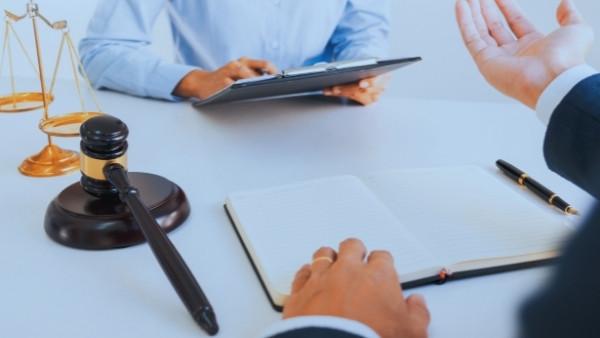 En advokat og en klient som diskuterer om rettshjelpsdekning i erstatningssaker etter yrkesskade