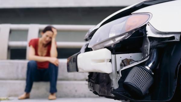 En kvinne sitter på fortauet etter en trafikkulykke som hun senere vil kreve en trafikkskadeerstatning for