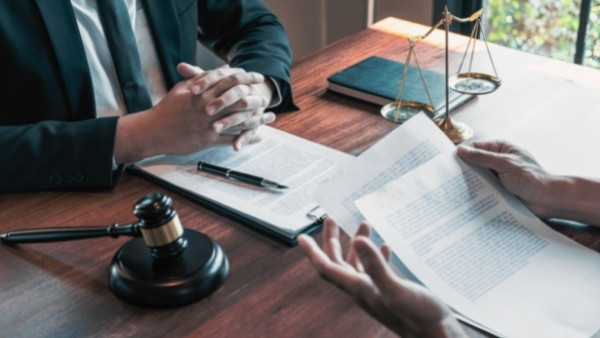 En mann som har fått avslag på sin søknad om yrkesskadeerstatning diskuterer med en advokat