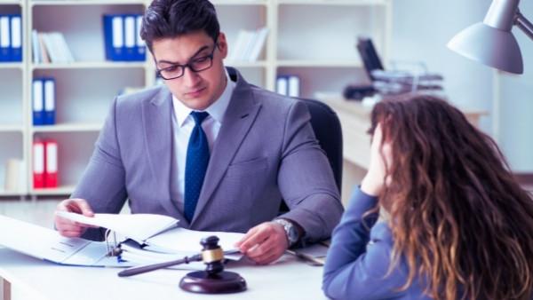 En kvinne som vil kreve gjenopptakelse av sin trafikkskadesak diskuterer med en advokat