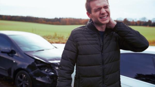 En mann med sterke smerter som holder en hånd på nakken etter å ha blitt utsatt for en trafikkulykke