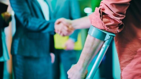 En mann som har blitt utsatt for en trafikkulykke og har behov for juridisk bistand for å fremme et erstatningskrav gir hånden til en advokat