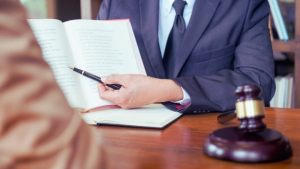En advokat som har erfaring på bilansvarlovas område diskuterer med en klient som trenger juridisk bistand